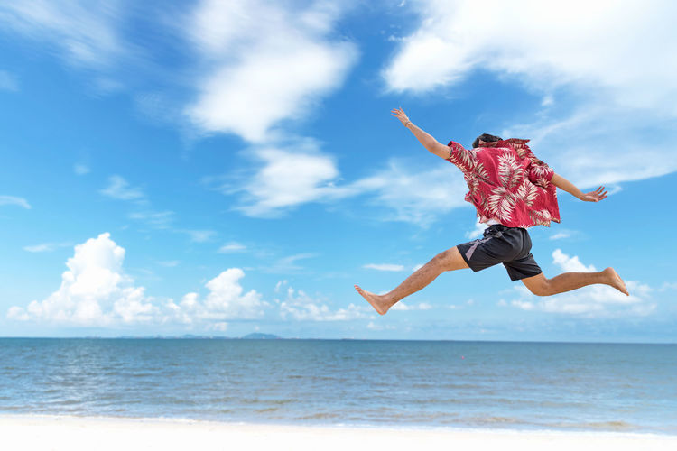 Low angle view of person jumping over sea against sky