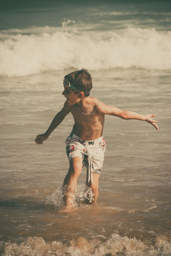 Shirtless Boy Playing At Beach