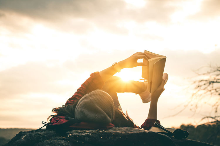 Woman reading book while lying on lakeshore during sunset