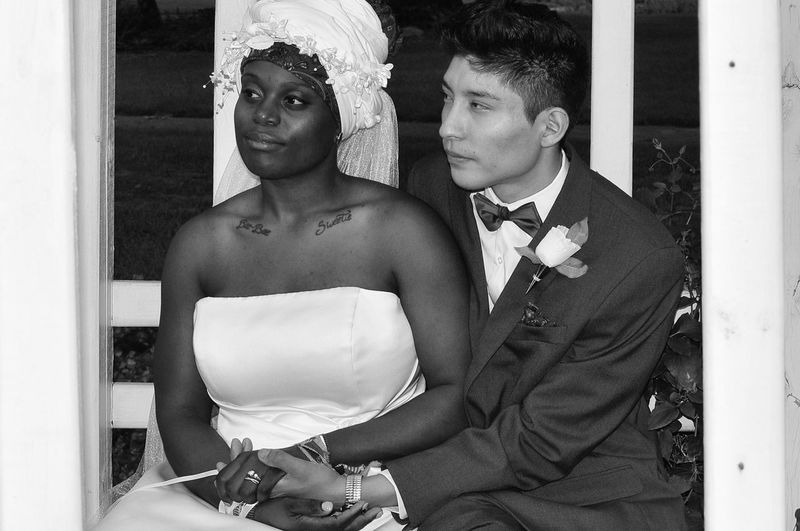 Well Dressed Bride And Groom Sitting Outdoors