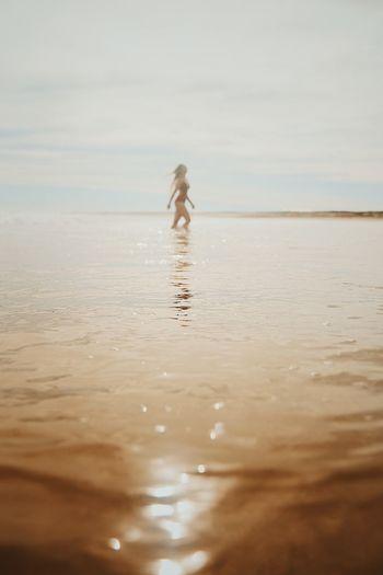 Woman In Sea Against Sky