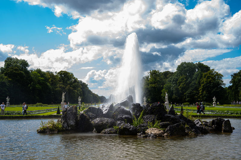 View of fountain in lake against cloudy sky