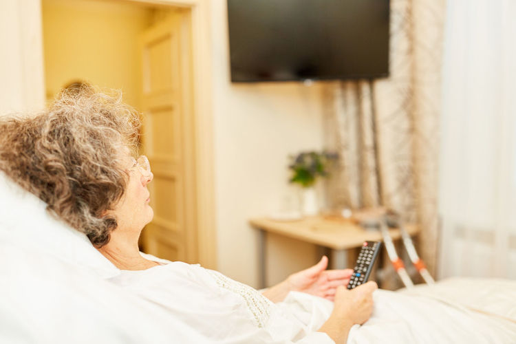 Midsection of woman holding mobile phone while relaxing on bed at home