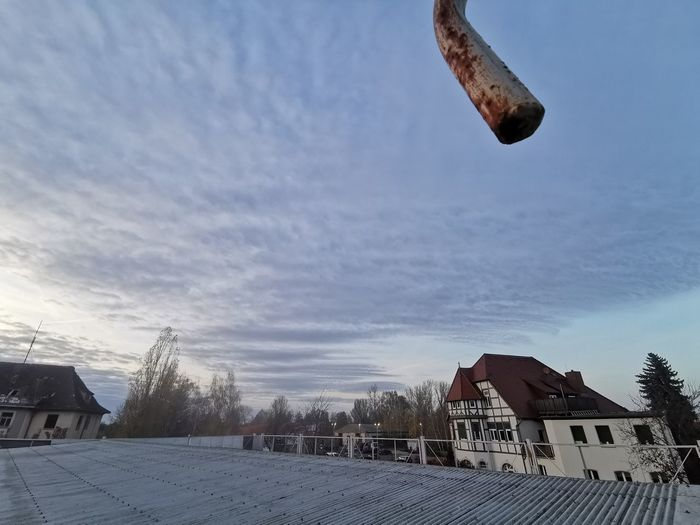 Houses by buildings in town against sky during winter