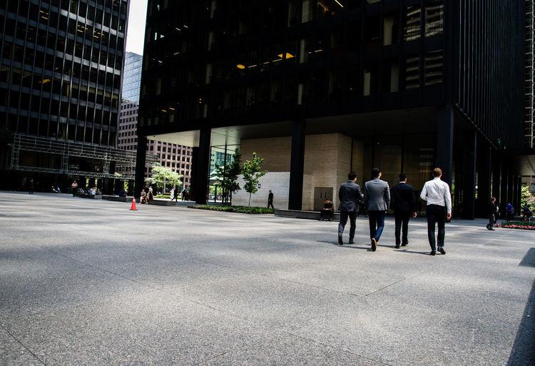 Businessmen Walking On Street In City
