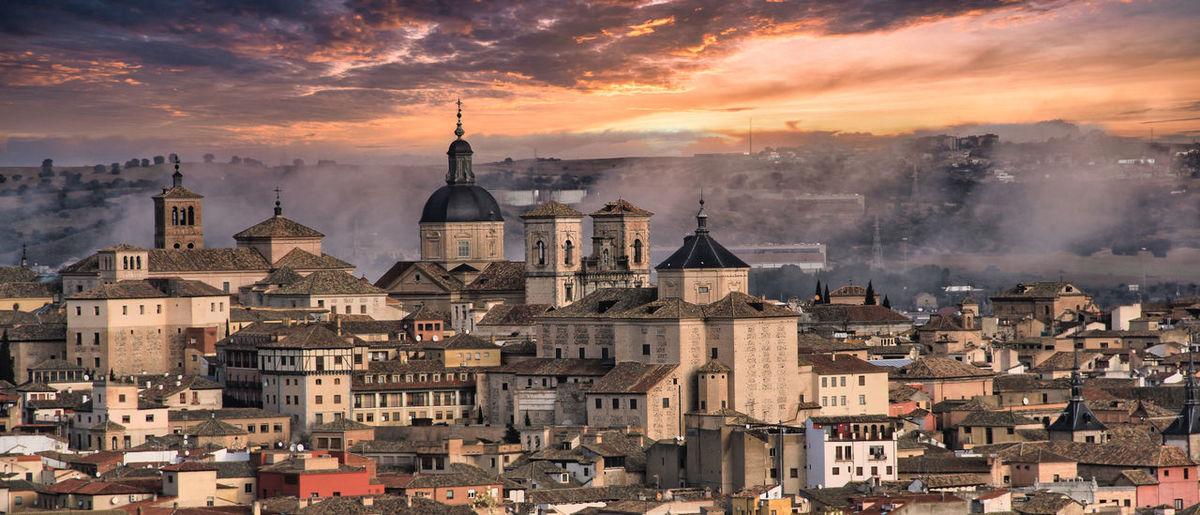 Aerial view of buildings in city of toledo, spain against sunlit cloudy sky