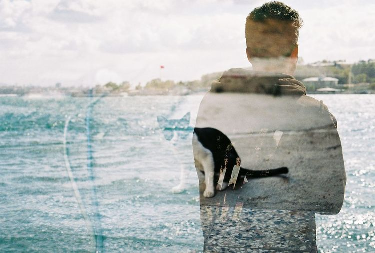 Double exposure of man and cat against sky