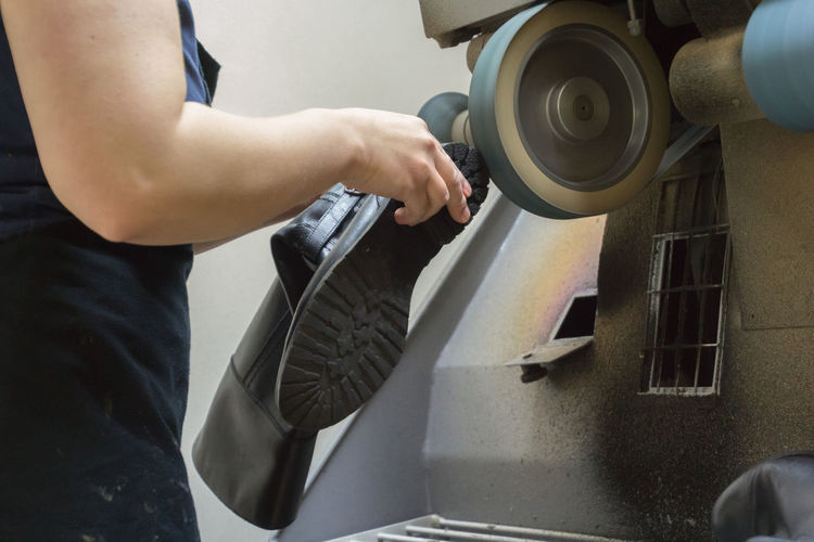 Midsection Of Woman Making Shoe At Workshop