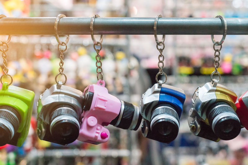 Close-up of camera key rings hanging for sale at market stall