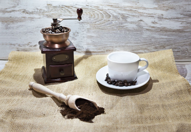 White cup and plate with beans, milling coffee and a wooden grinder on rustic background with copy space. Indoors  No People Still Life Table Coffee Beans Grinder Millennial Pink Milling Aroma Background Wallpaper Copy Space Vintage Retro Caffeine Cafe Bare Tree Beverage Rustic Brown Wooden Capuccino Expreso Breakfast
