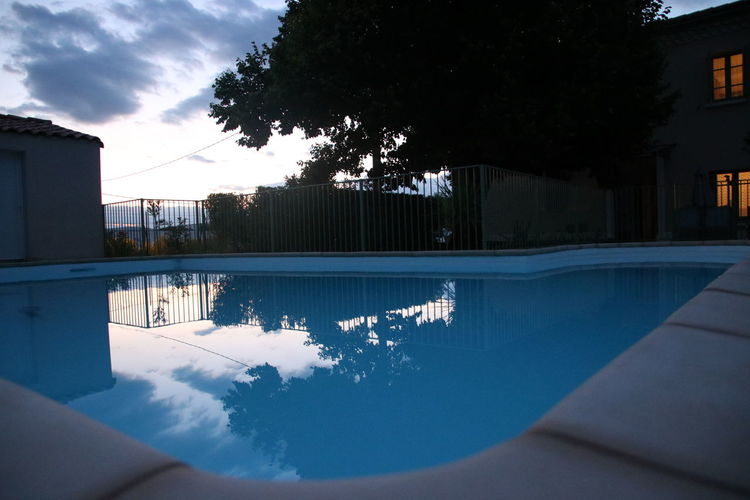 Reflection of trees in swimming pool against sky