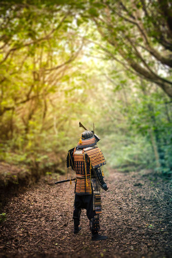 Rear view of man wearing samurai costume amidst trees in forest