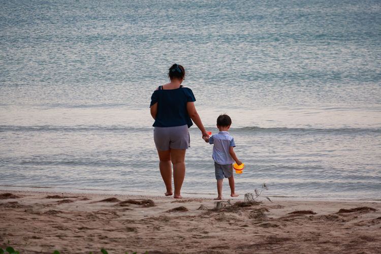 Mother and son walking on shore against sea at beach