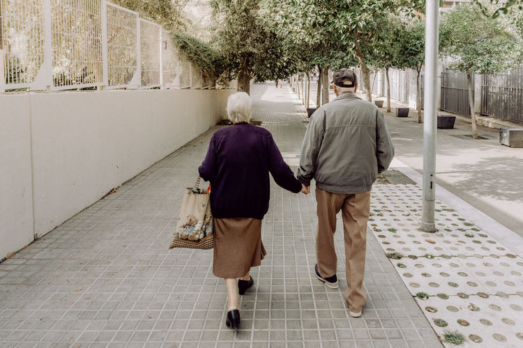 together we are one The Street Photographer - 2018 EyeEm Awards Walking Around Taking Photos City City Life From Behind Barcelona SPAIN Street Streetphotography Street Photography EyeEm Best Shots Eye4photography  EyeEm Gallery Travel Explore Full Length Bonding Senior Couple Holding Hands Silver Surfer Mature Couple Couple Couple - Relationship Retirement
