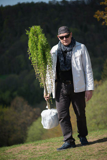 Man holding potted a larch tree Gardener Gardening Casual Clothing Day Fashion Field Focus On Foreground Front View Full Length Glasses Holding Land Larch Tree Leisure Activity Lifestyles Nature One Person Outdoors Plant Potted Plant Real People Standing Tree Young Adult Young Men
