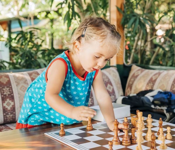 Cute girl playing chess at backyard