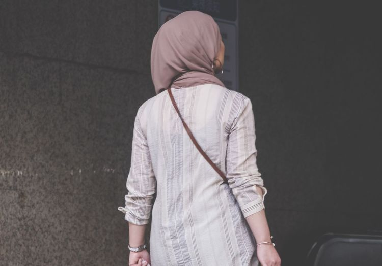 Rear view of woman wearing hijab while standing against wall