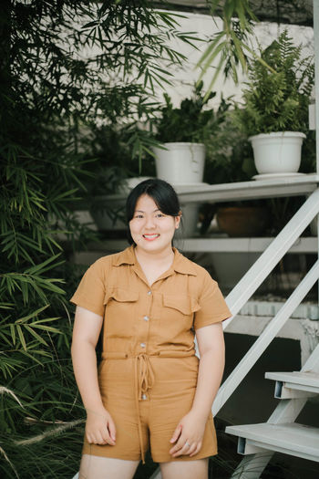 Portrait of a smiling young woman standing against plants