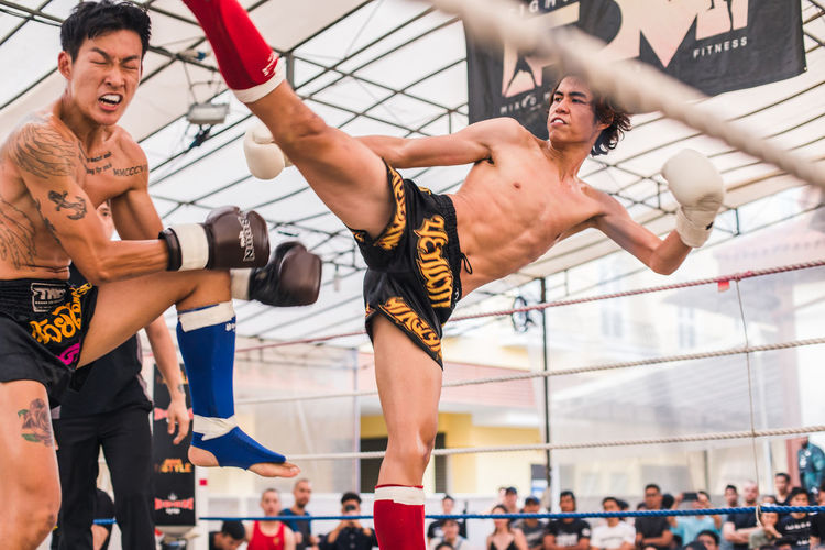 High Kick Real People Lifestyles Sport Adult Strength Men Vitality Healthy Lifestyle People Competition Shirtless Young Adult Determination Effort Crowd Fighting Muay Thai Boxing - Sport