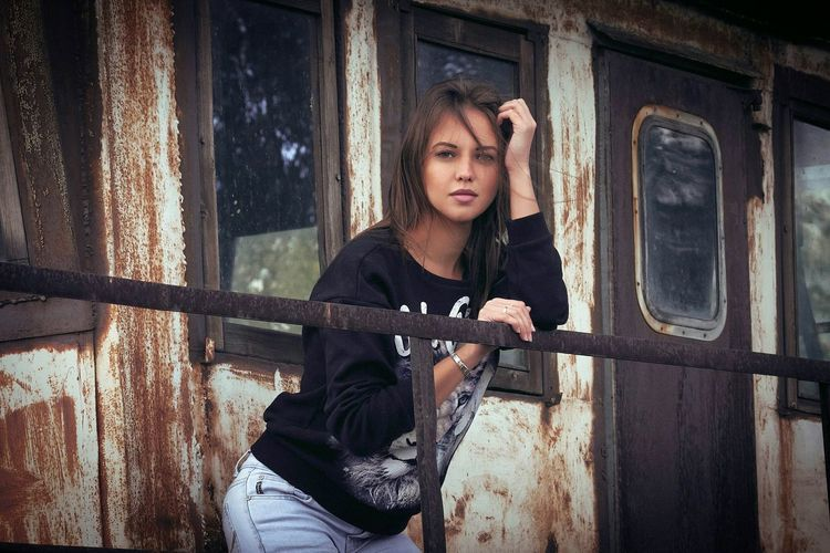 Portrait Of Young Woman Standing Outside Abandoned House
