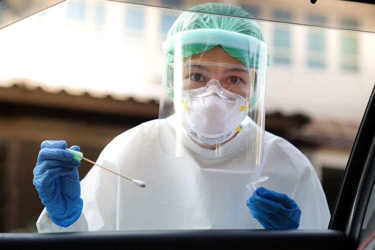 Portrait of doctor wearing protective workwear holding medical equipment seen through car window