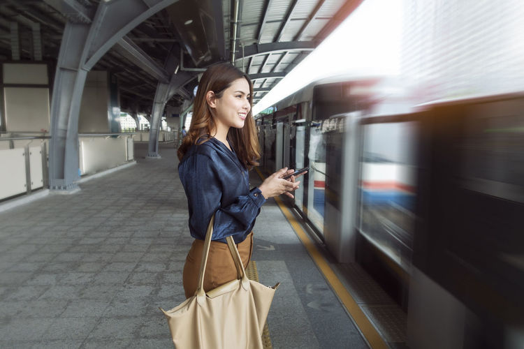 Young woman using mobile phone while standing on train