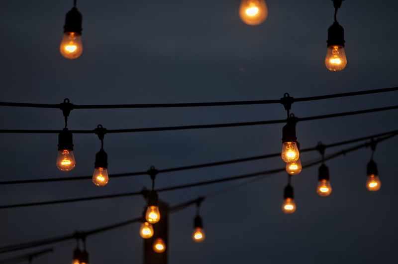 Low angle view of illuminated lamps against sky at night