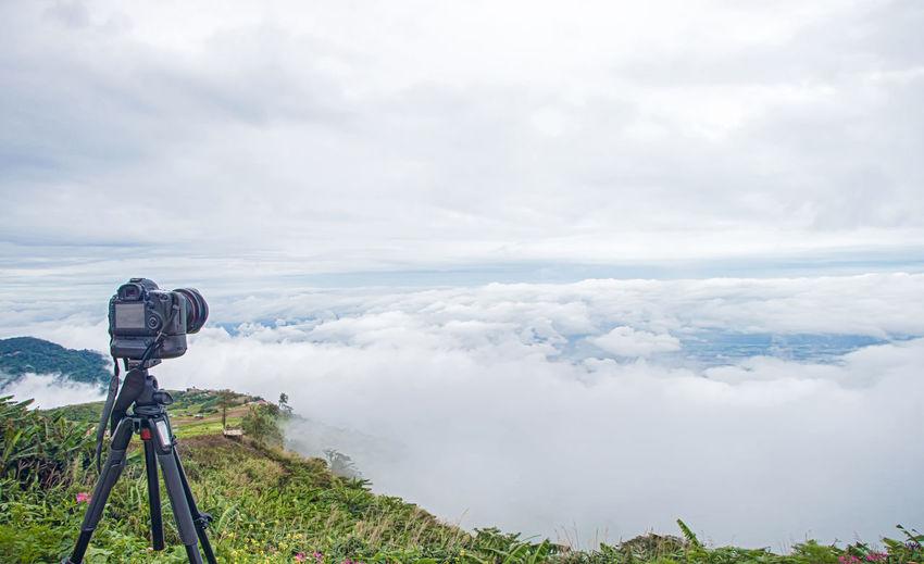 Close-up of camera on landscape against sky