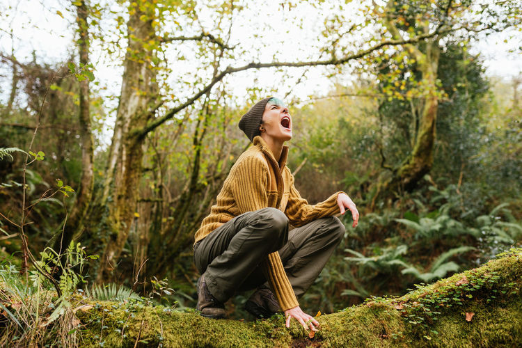 Young woman looking away while sitting on tree in forest