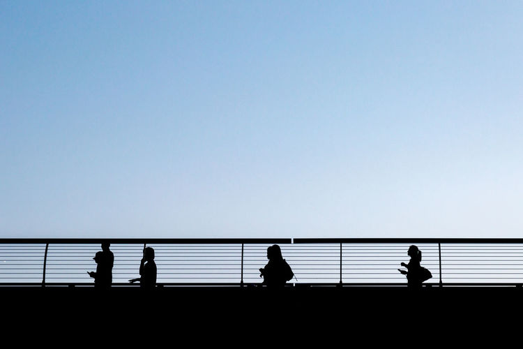 Silhouette People On Bridge Against Clear Blue Sky
