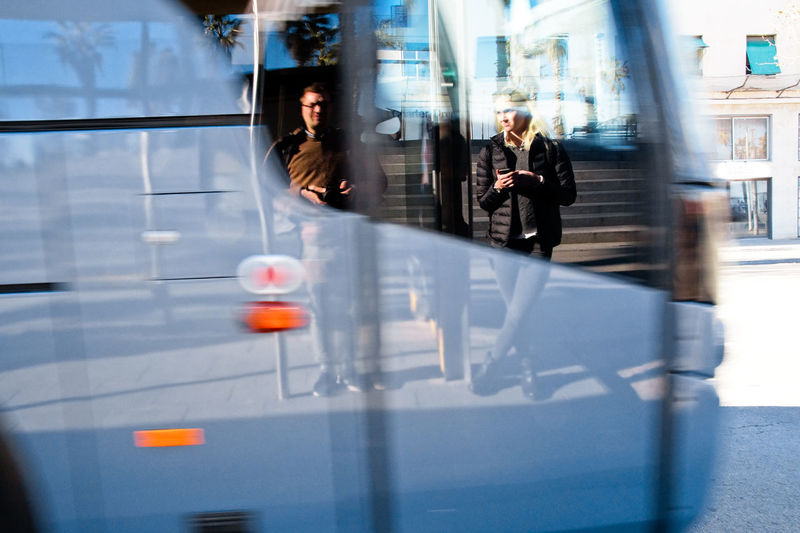 Reflection of people seen in moving bus at city