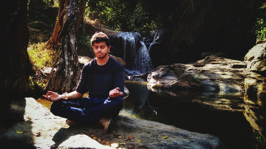 Full length of young man meditating on rock in forest