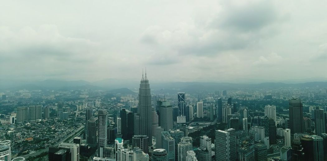 Kuala lumpur cityscape against cloudy sky