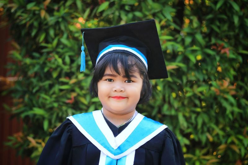 Portrait Of Smiling Cute Girl Wearing Graduation Gown