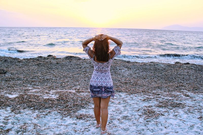 Rear view of woman standing at beach against sky during sunset