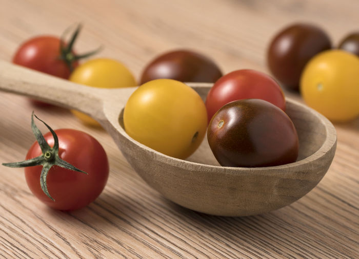 Cherry tomatoes in a variety of colors in wooden spoon. On a wooden table. Fresh; Food; Healthy; Ripe; Red; Vegetable; Cherry; Tomato; Vegetarian; Yellow; Diet; Orange; Variety; Colorful; Different; Health; Green; Organic; Ingredient; Many; Summer; Small; Juicy; Raw; Nature; Tomatoes; Color; Natural; Closeup; Background; Agricul Food Healthy Eating Food And Drink Wellbeing Fruit Vegetable Indoors  Bowl Tomato No People Wood - Material Freshness Table Close-up Still Life Studio Shot Ingredient Raw Food Household Equipment Red