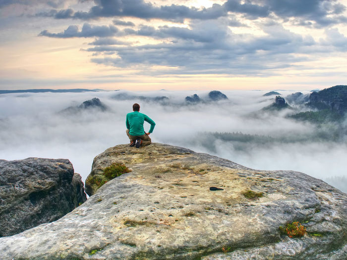Professional photographer on knees at tripod look into fall land and thinking. hiker with tripod