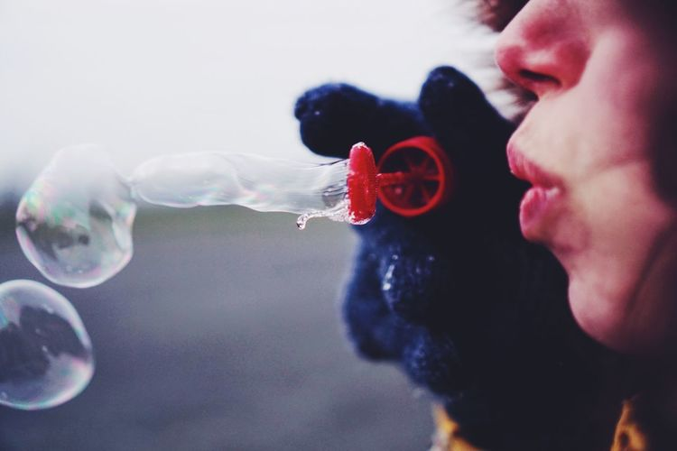 Close-up of woman blowing soap bubble