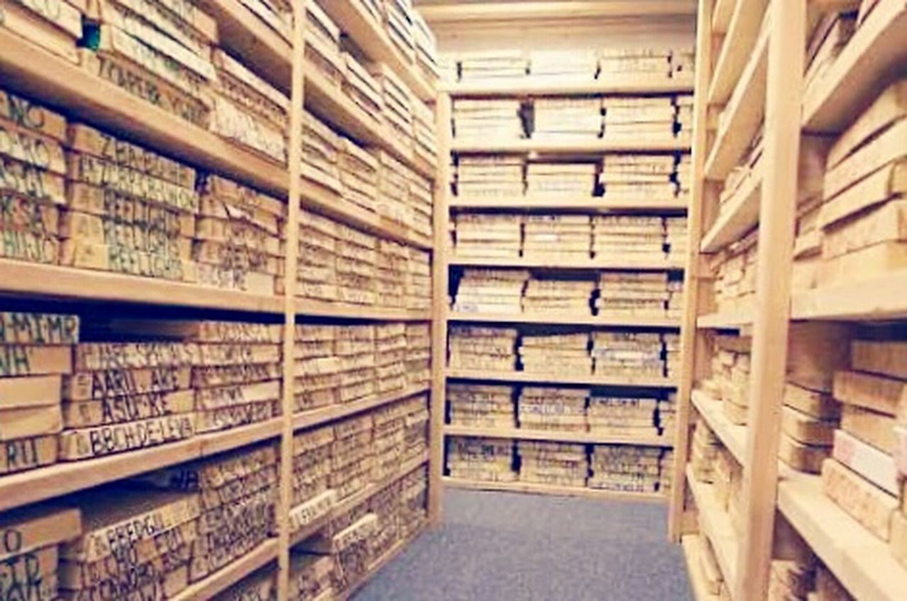 shelf, data, filing cabinet, library, archives, storage room, indoors, storage compartment, bookshelf, cellar, basement, warehouse, history, collection, file, large group of objects, information medium, stack, in a row, research, cabinet, business, office, straight, photograph, no people