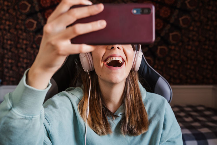 Cheerful woman talking on video call at home