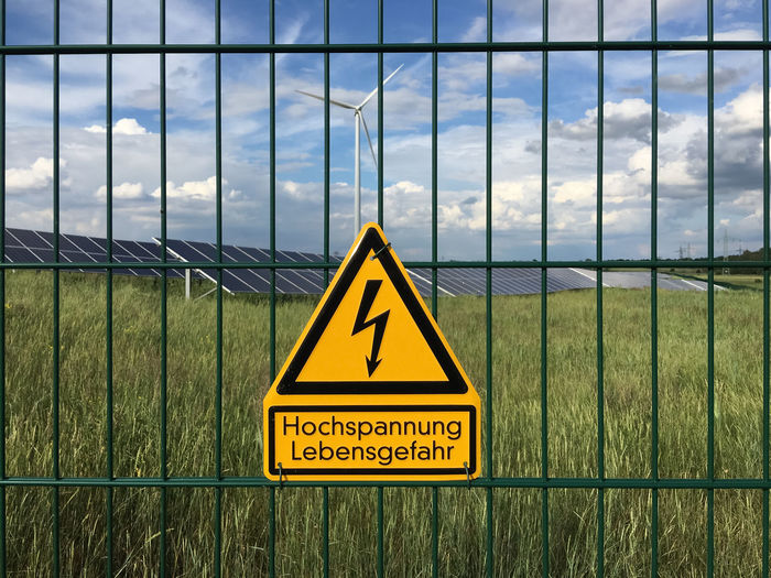 fence with high voltage sign and solar plant Chainlink Fence Cloud Cloud - Sky Cloudy Danger Fence Focus On Foreground Grass High Voltage High Voltage Sign Information Sign Nature Sign Sky Sky And Clouds Solar Solar Energy Solar Energy Plant Solar Plant Voltage Warning Warning Sign Warningsign Wind Turbine Yellow