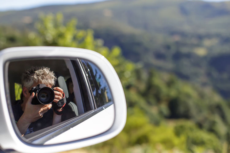 Reflection Of Man Photographing On Side-View Mirror Of Car