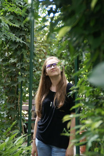 Botanical Gardens Green Color Tree Beautiful Woman Bush Casual Clothing Day Eyeglasses  Flower Garden Growth Leaves Leisure Activity Lifestyles Long Hair Nature One Person Outdoors People Plant Real People Smiling Standing Tree Young Adult Young Women Perspectives On Nature