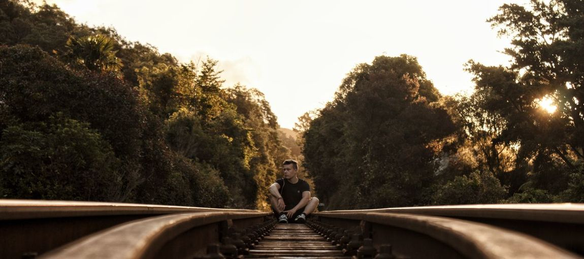 Young man sitting on railroad track against clear sky