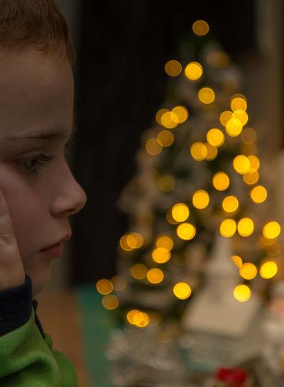 Rear view of boy looking at illuminated christmas tree