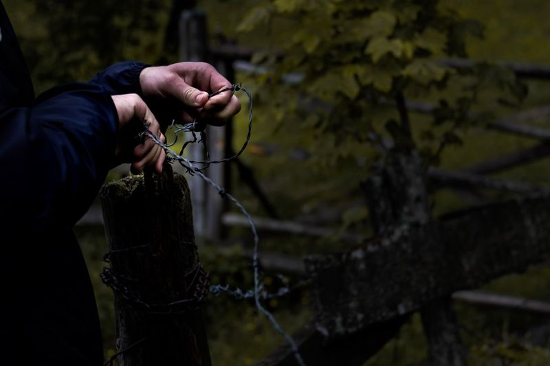 Midsection of person holding barbed wire