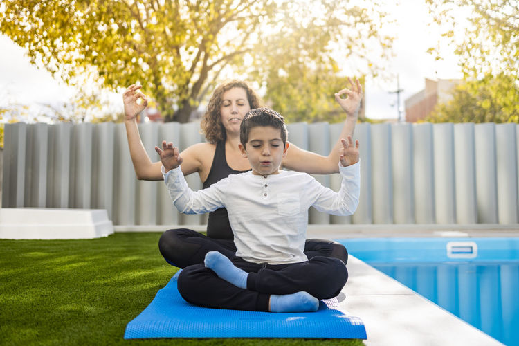 Mother and son doing yoga exercises in their home garden