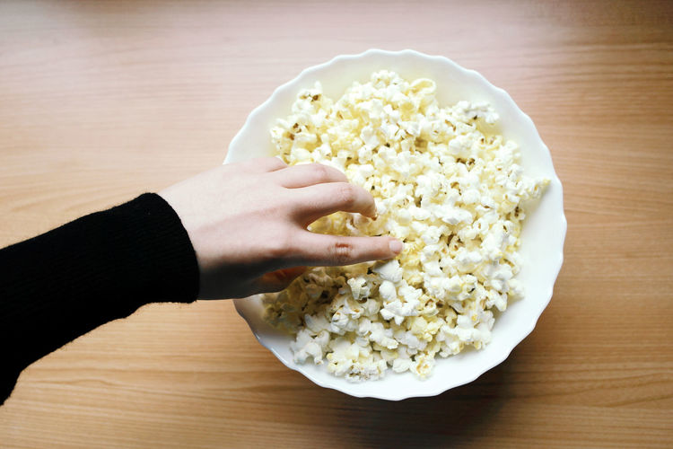 Cropped hand having popcorn on table