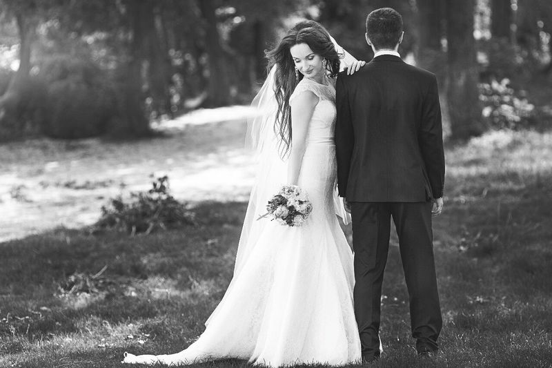Side view of bride holding bouquet while standing with groom on grassy field