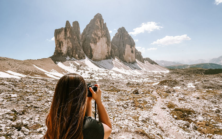 Woman photographing rock on mountain against sky